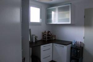 Buanderie avec fenêtre de 9.60m² aménagée avec un grand placard (machine à laver et rangements), un plan de travail et des meubles de rangement. Meubles à chaussures également. Accès au garage par cette pièce.