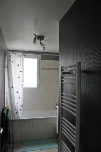 Salle de bain avec meuble double vasques, baignoire et sèche-serviettes. 4,64 m²